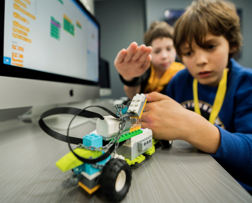 Young boy focuses on operating a robot he coded at iCode