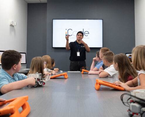 Young male instructor teaches classroom of children to code robots using tablets