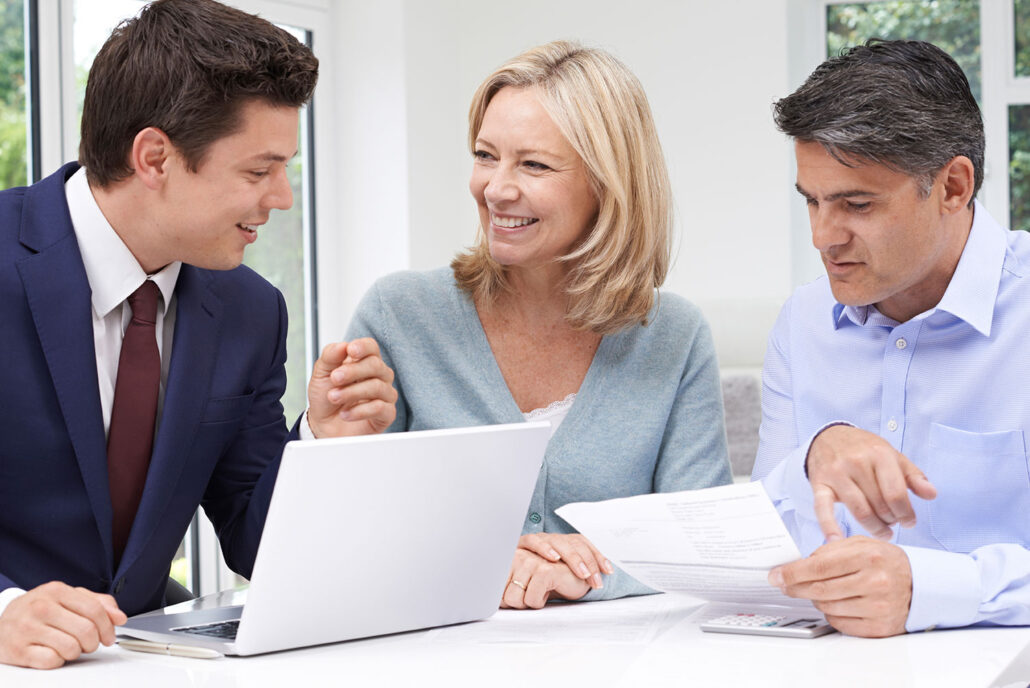 Two men and one woman discuss paperwork to become an iCode franchise owner