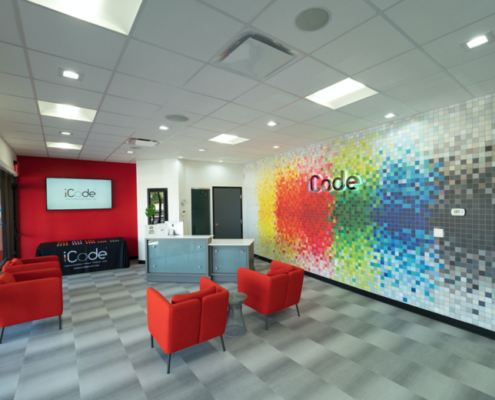 iCode franchise lobby with red furniture and bright, multi-colored walls