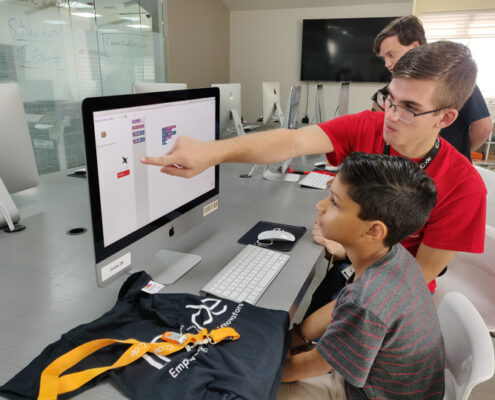 Young iCode franchise instructor teaches child how to code on a computer