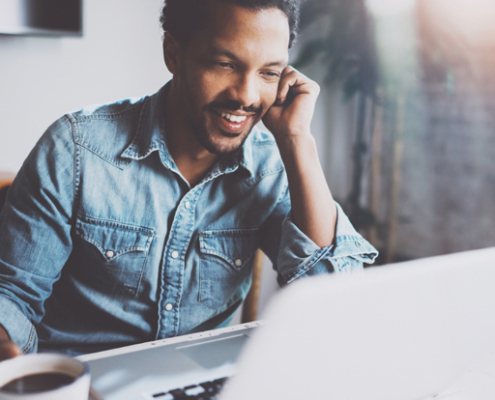 Happy man on a computer enjoys his coffee while working on his business
