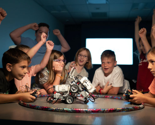 Kids compete with robots they designed at iCode while other children cheer