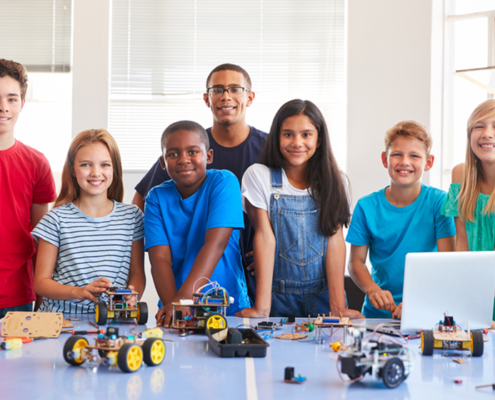 Group of iCode students standing behind a table displaying small robots they've built