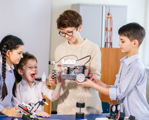 Four children holding a robot they've help construct at an iCode education franchise