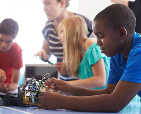 Child works on robot in coding class